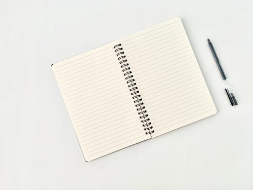 Spiral notepad with lines near pen on white background