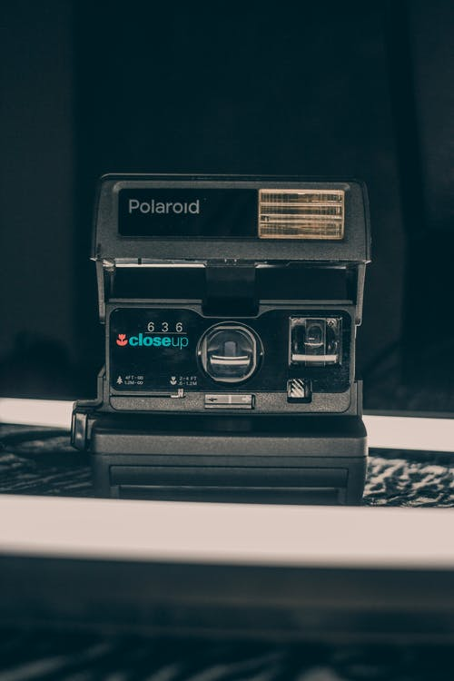 Old fashioned instant camera with focus lens and instant print placed on desk in studio