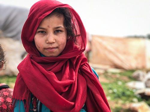 Pensive ethnic girl in headscarf in countryside
