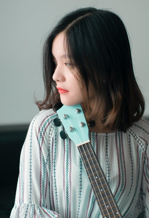 Dreamy young ethnic female musician with electric guitar