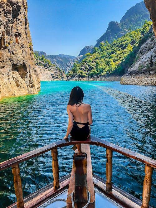Woman in Black Bikini Sitting on Brown Wooden Railings Near Body of Water