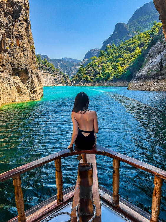 Woman in Black Bathing Suit Sitting on Boats Railing