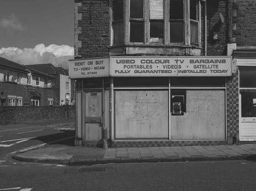 Black and white of old abandoned building with vintage shop of used electronic goods on empty street of city