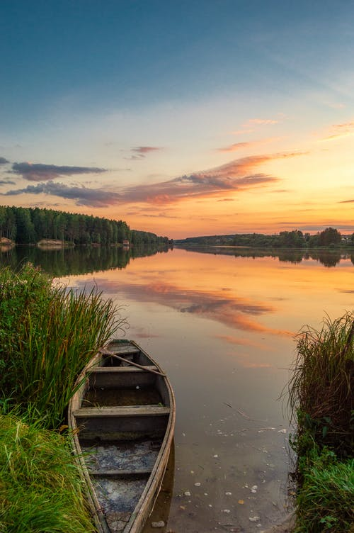 Wooden boat on calm lake reflecting spectacular sunset sky