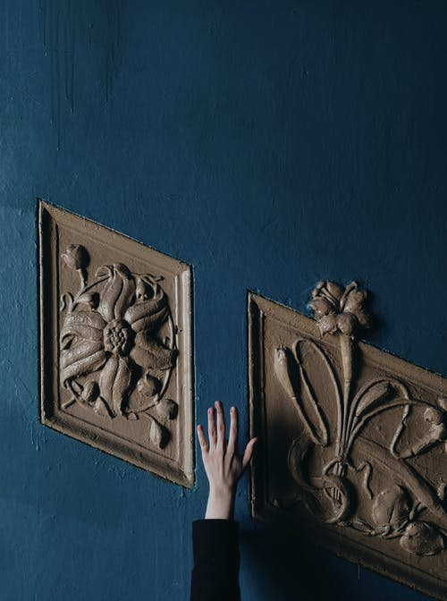 Person Holding Brown Wooden Floral Carved Wall Decor
