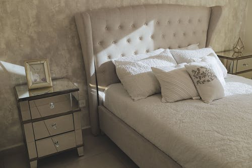 White Bed with Pillows in Between Side Tables