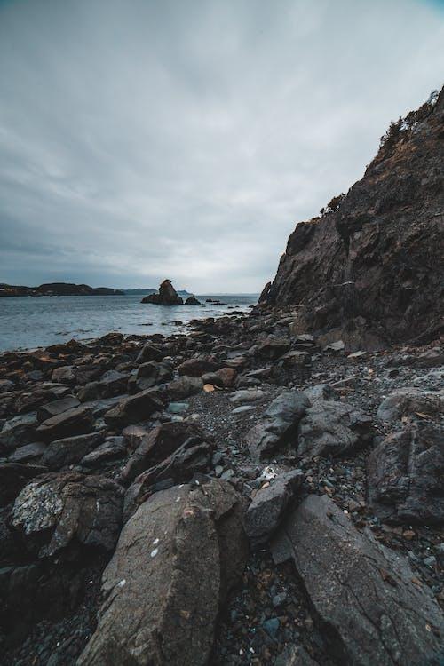Empty gray rocky coast and stony cliff against calm sea and cloudy sky