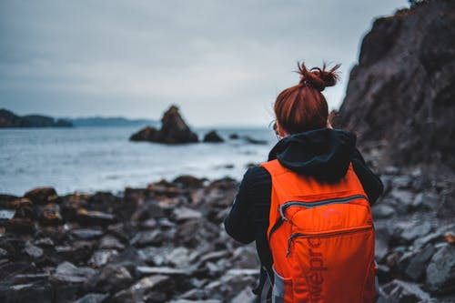 Traveler with backpack standing on rocky shore