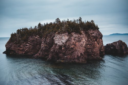 Rocky cliff in sea during cloudy day