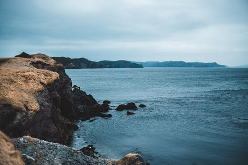 High angle of rough stony coast with steep slopes near calm sea and mountains on horizon