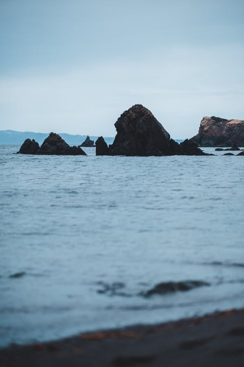 Rocky cliffs in sea in gloomy day