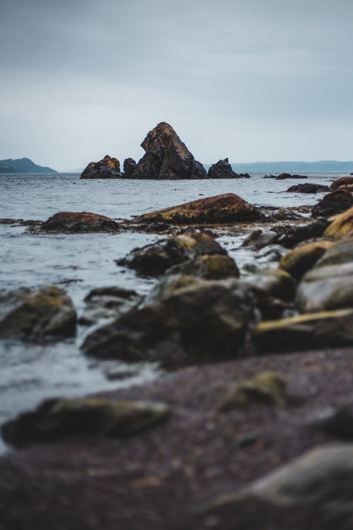 Lonely rocky seashore in cloudy day