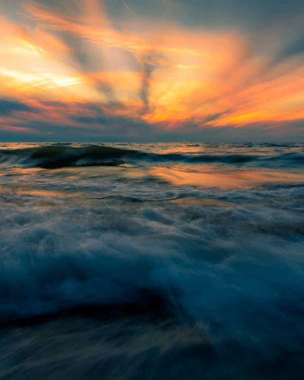 Cloudy bright sunset sky over stormy sea