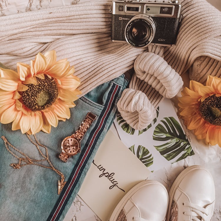 Top view layout of jeans sunflowers vintage photo camera and accessories placed on jeans and sweater near sneakers