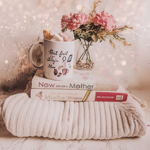 Mug of coffee on knitted sweater and books