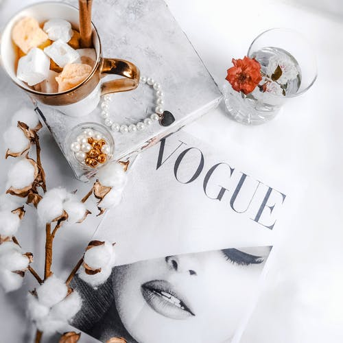 Top view of fashion magazine placed near coffee cup with metal tube and fluffy cotton branch with accessories