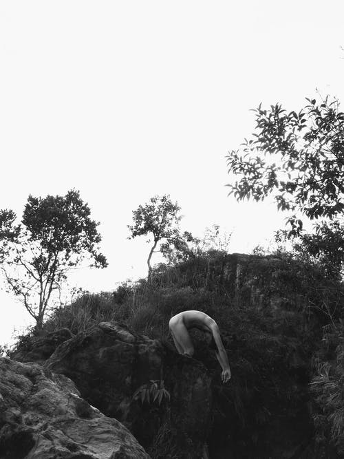 Black and white side view of naked person ready to jump in water from stony cliff