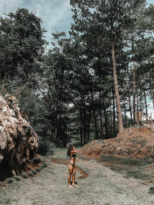 Woman in Black Tank Top and Black Shorts Standing on Brown Dirt Road Between Green Trees