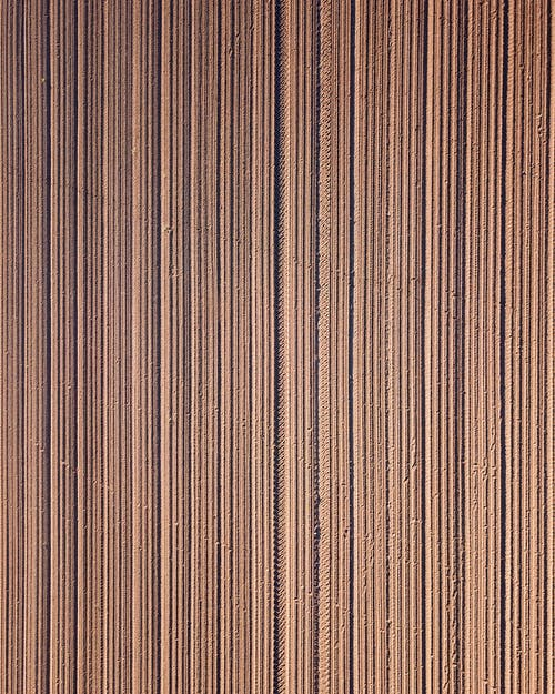 Overhead of textured backdrop representing brown ploughed meadow with vertical lines in countryside in daylight