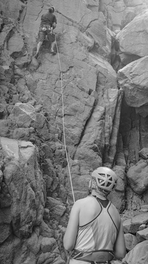 Unrecognizable alpinist climbing rough rock with friend