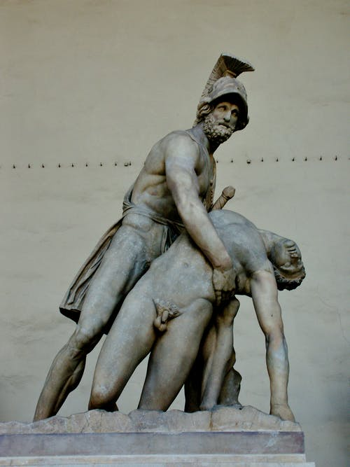 Aged marble statue of Menelaus supporting naked body of Patroclus on pedestal in Florence