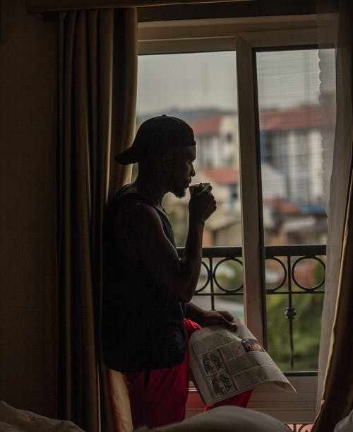 A Man Drinking and Holding a Newspaper while Looking outside the Window