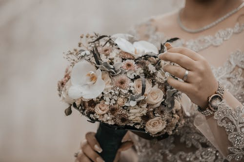 Crop unrecognizable woman in elegant wedding dress and accessories with bridal bouquet during festive event
