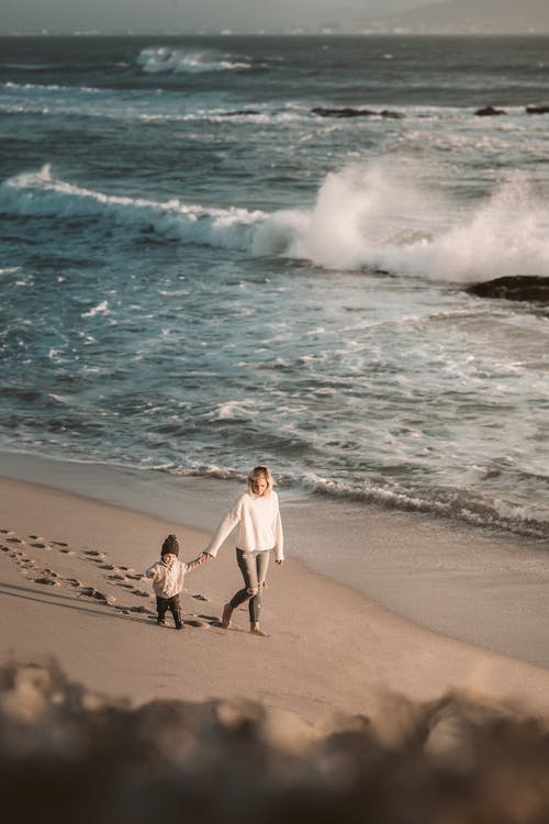 A Mother Walking on the Beach with Her Child While Holding Hands