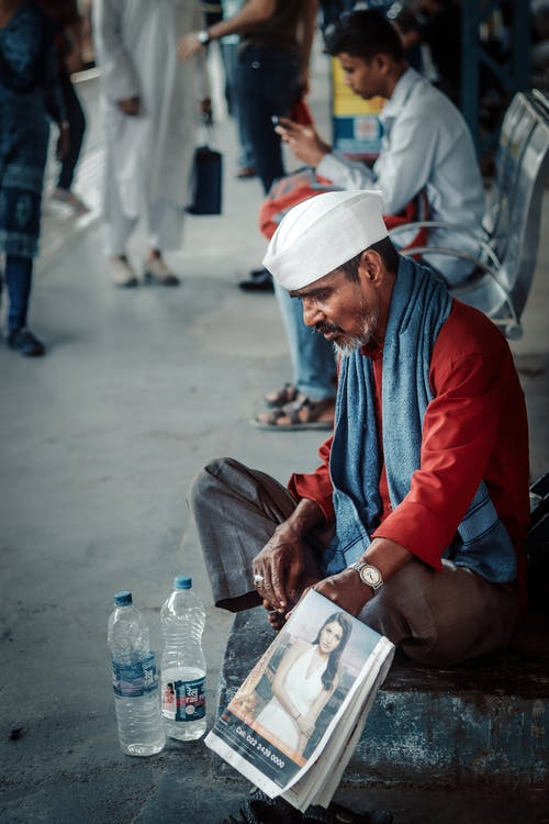 A Man Sitting and Holding a Newspaper