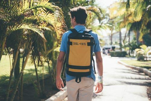 Man in Blue and Black Backpack Walking on Sidewalk