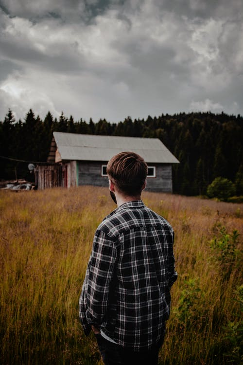 Unrecognizable man in field behind house in autumn