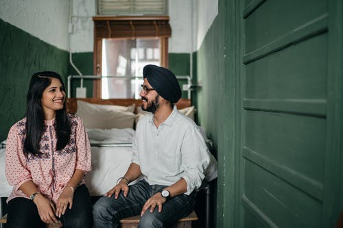 Smiling Indian couple in casual clothes and turban sitting on bench against bed in narrow green bedroom and chatting while looking at each other happily