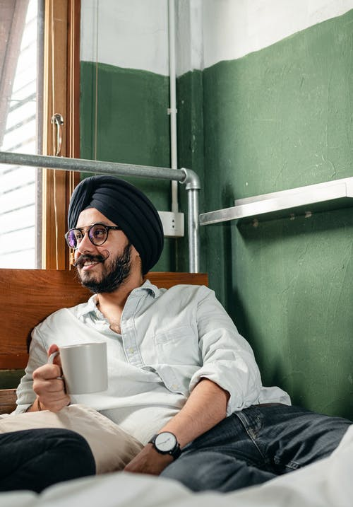 Cheerful man in turban and eyeglasses resting on bed