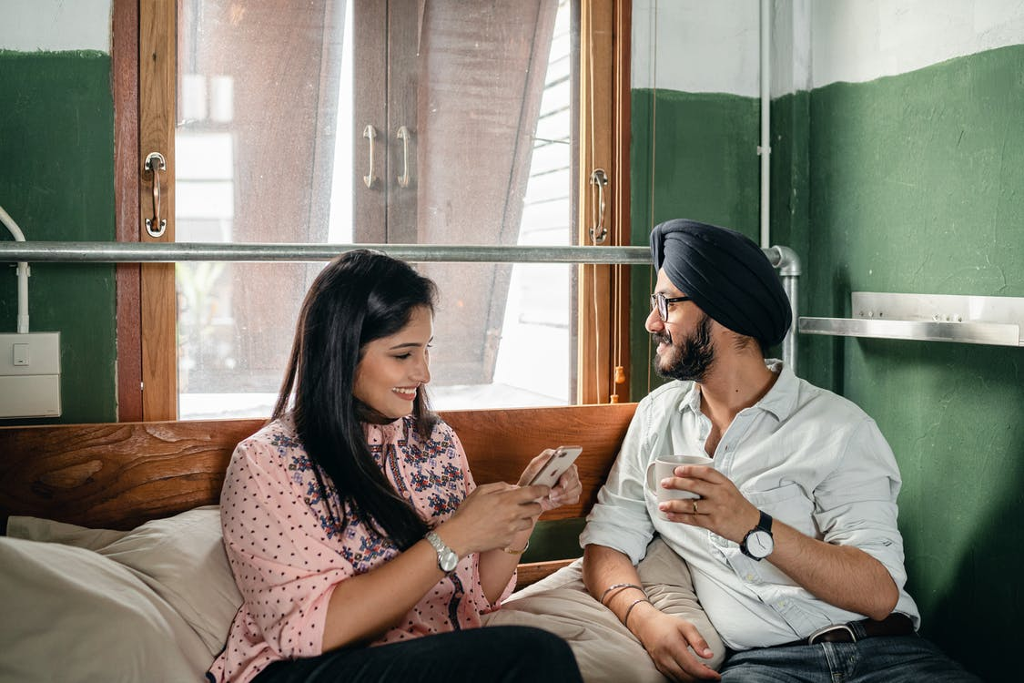 Optimistic smiling excited Indian couple in casual clothes and turban using mobile phone and chatting while relaxing on comfortable bed in sunny room