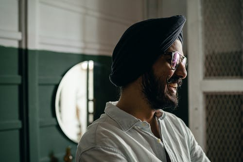 Side view of bearded positive laughing Indian male in eyeglasses wearing casual shirt and turban standing near green and white wall and mirror and looking away happily