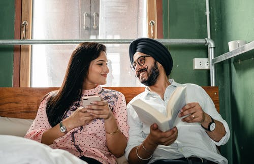 Cheerful couple with book and smartphone on bed