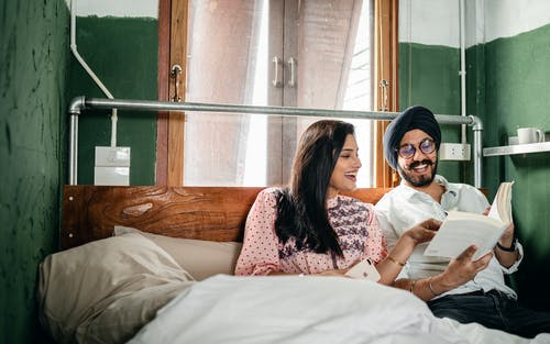 Cheerful Indian couple reading book in bedroom