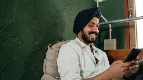 Happy male of Indian descent smiling while messaging on cellphone