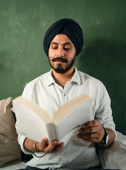 Focused ethnic man reading book on couch