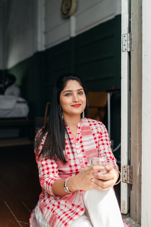 Happy young Indian female in long red and white checkered shirt and white pants sitting on threshold of house with glass of water and looking away on sunny day