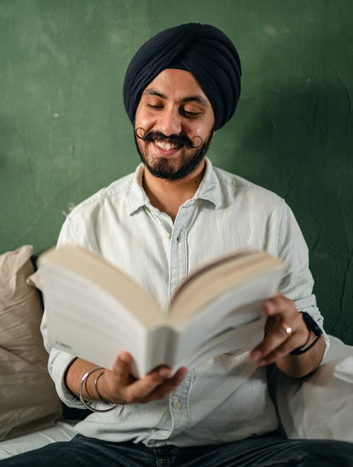 Positive young man of Indian descent in casual outfit reading amusing story and smiling while sitting on sofa in studio