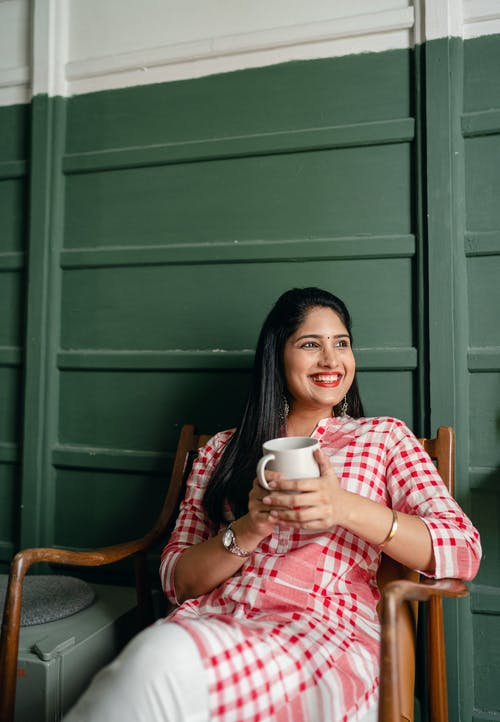 Positive charming young Indian lady in traditional pink and white wear resting on wooden chair with cup of hot beverage and looking away happily