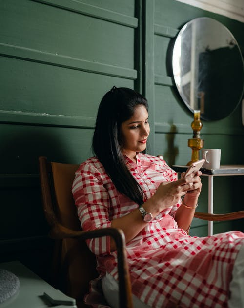 Pensive woman in traditional Indian outfit using smartphone