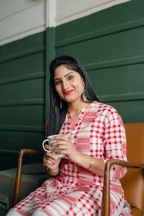 Positive smiling Indian lady in stylish traditional wear sitting on chair against green wall with cup of hot drink and looking at camera