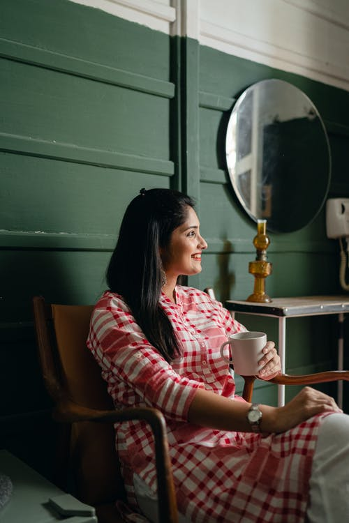 Side view of young positive Indian lady in trendy traditional clothes resting on chair with cup of drink against green wall near mirror