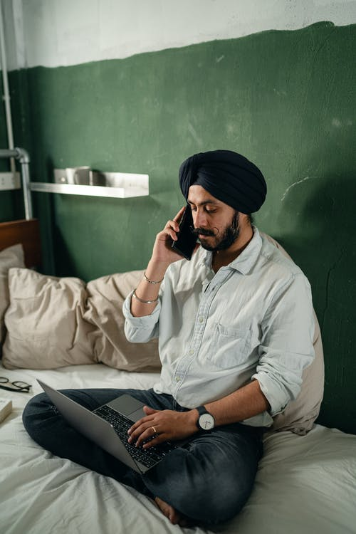 Focused bearded Indian male freelancer wearing turban sitting on bed against green wall in old room and having conversation via cellphone while working on netbook remotely
