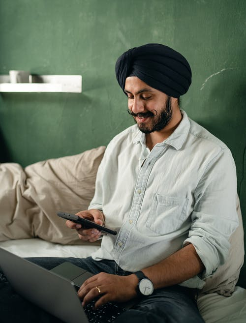 Positive man using laptop and smartphone on bed