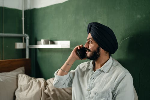 Side view of handsome Indian male engaged in pleasant phone conversation while sitting in simply furnished room and looking away smiling softly