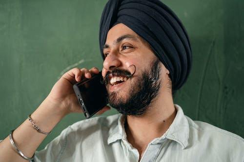 Cheerful Indian man talking on cellphone and looking away