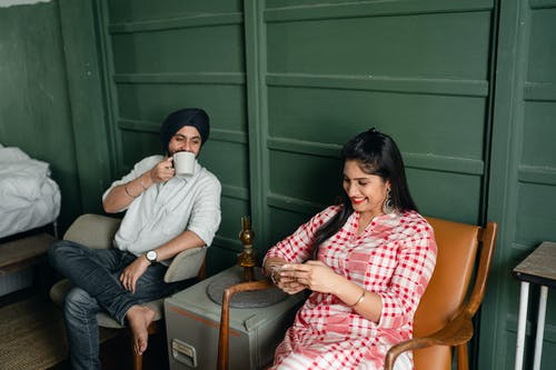 Young Indian spouses relaxing and discussing Internet news at home